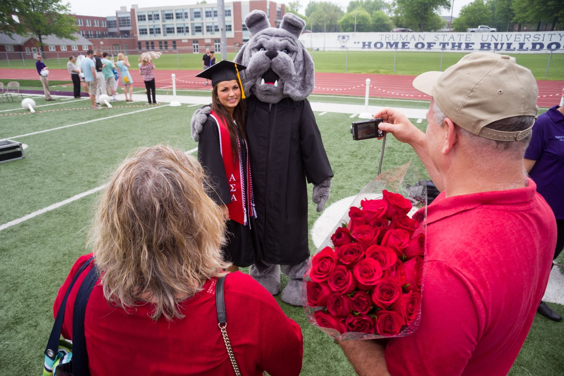 Parents taking photo of Truman graduate with the mascot