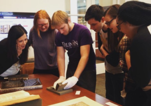 Students in the Italian Civilization II class examine a 1593 edition of a book as part of their investigation into Early Modern print culture in Italy