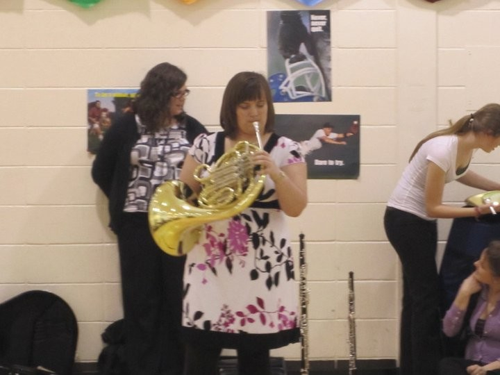 Horn student performing for an elementary assembly