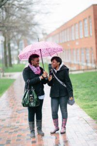 students sharing umbrella