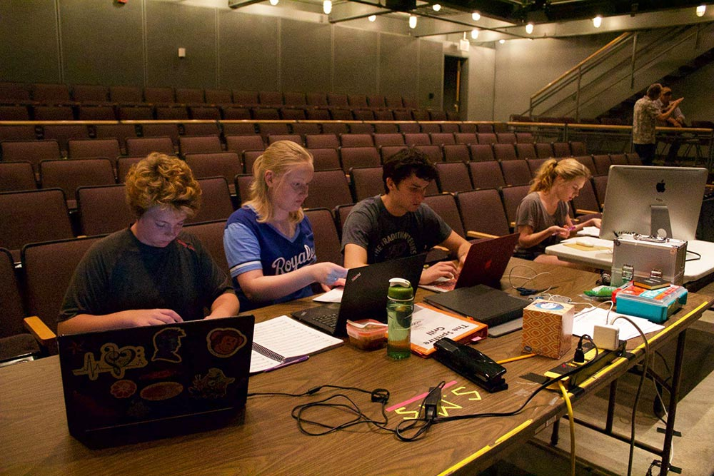 Four students at a table working on laptops