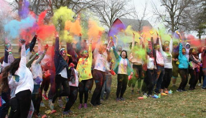 Students celebrating the Holi Festival with brightly colored powder