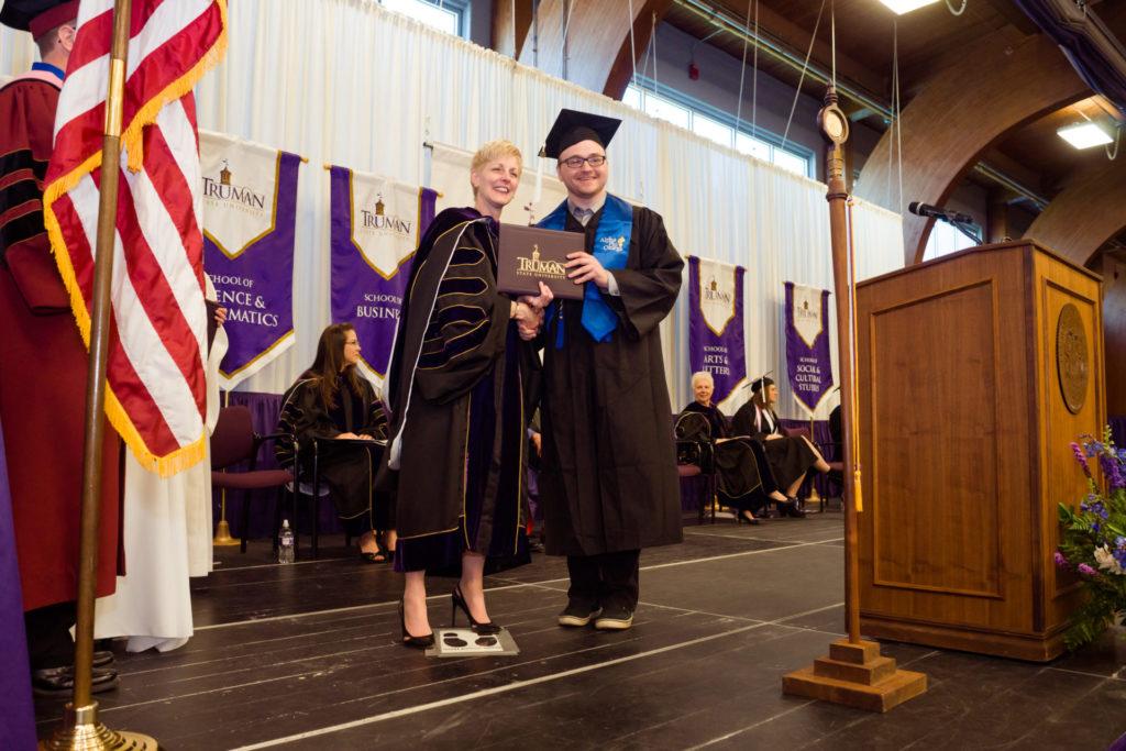 President Sue Thomas presenting a diploma