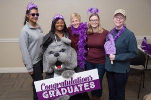 President Thomas and graduating students at the senior pizza party