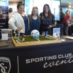 Three people at a publicity table at an event promoting Sporting club events
