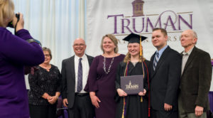 Truman graduate in cap and gown along with friends and family who attended the Commencement ceremony