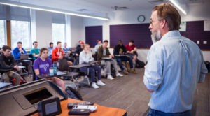 Professor standing in front of students sitting in a classroom