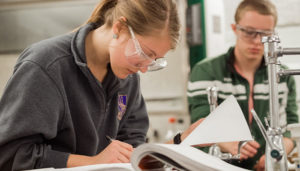 Student with lab googles makes notes in a book