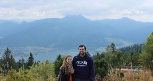 Two people standing on a mountain with view of lake
