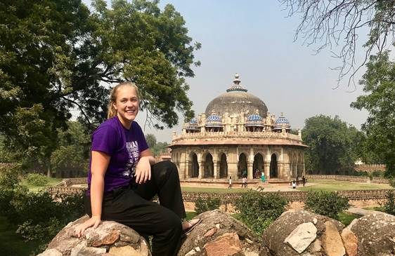 Girl sitting on a rock with a temple in background
