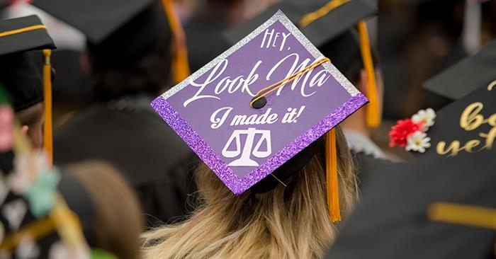 Person wearing graduate cap that says