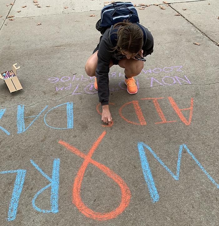 Girl writing a chalk message on sidewalk